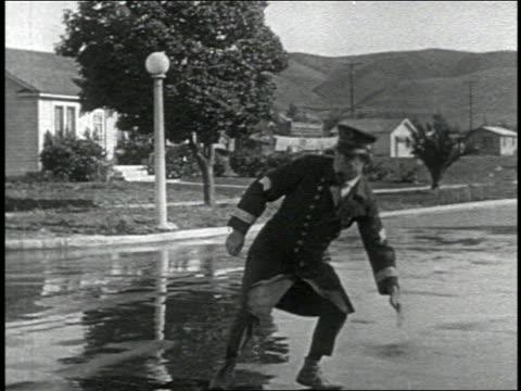 b/w 1924 long shot keystone kop (will rogers) falling off horse skidding in street / standing up / 2 shots - pflanzenfressend stock-videos und b-roll-filmmaterial