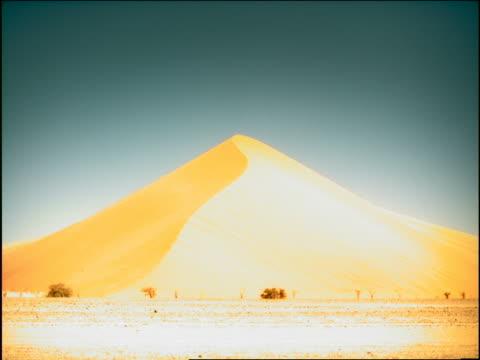 vídeos de stock e filmes b-roll de overexposed long shot large sand dune in desert / namibia, africa - super exposto