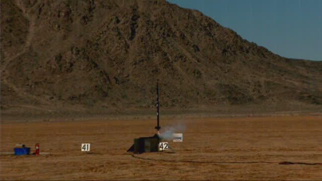 stockvideo's en b-roll-footage met long shot, locked down - a rocket launches from a desert / usa - raket wapen
