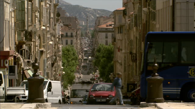 Long Shot Locked Down - Long, straight Marseille city street with munumental column in distance  / Marseille France