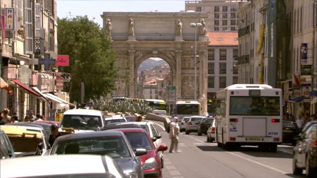 vidéos et rushes de long shot locked down - marseille city street with view of the sculptured porte d'aix arch  / marseille france - marseille