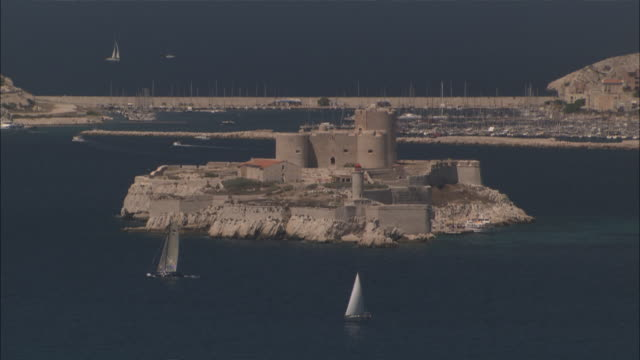 vidéos et rushes de long shot locked down - the chateau d'if fort on a small island surrounded by blue mediterranean waters and sailboats / marseille france - chateau