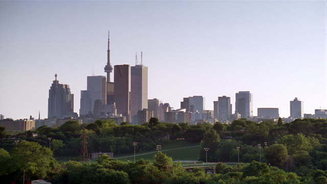 Long shot looking west across park at Toronto skyline at twilight