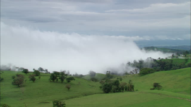 Long shot low clouds rolling over countryside / Sabotay, Costa Rica