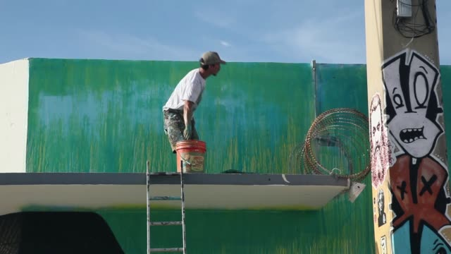 Long Shot Luis Valle works on a painting on the side of a building in the Wynwood section of Miami on August 12 2013 Murals by renowned street...