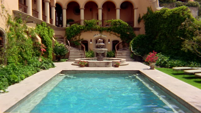vidéos et rushes de long shot man and two women holding hands + jumping into pool in courtyard with fountain in background - palace