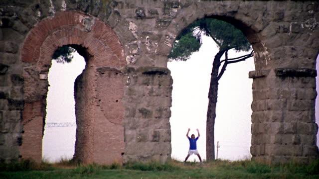 long shot man doing jumping jacks under roman aqueduct ruin arch / italy - hampelmannsprung stock-videos und b-roll-filmmaterial