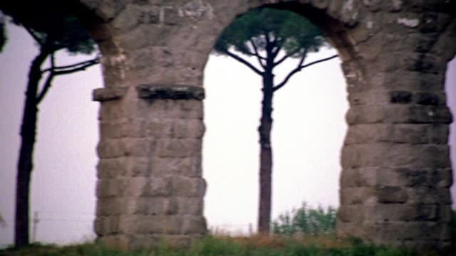 long shot pan man doing jumping jacks under roman aqueduct ruin arch / italy - hampelmannsprung stock-videos und b-roll-filmmaterial
