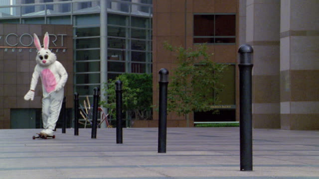 long shot man in rabbit costume skateboarding between poles in office building complex / los angeles, ca - hobby stock-videos und b-roll-filmmaterial