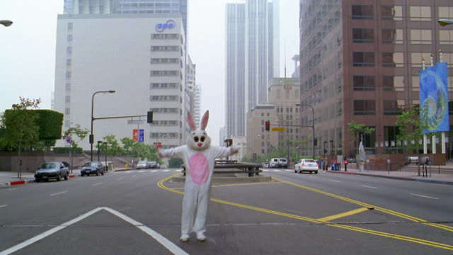 long shot man in rabbit costume standing in street and running towards camera with hands in air / l.a. - rabbit costume stock videos & royalty-free footage