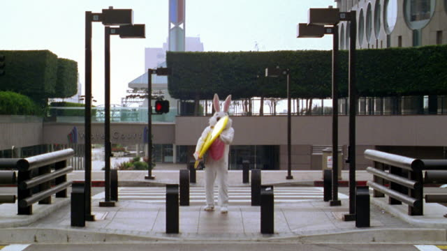long shot man in rabbit costume standing with surfboard before crossing street / los angeles, ca - エキセントリック点の映像素材/bロール