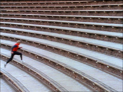 stockvideo's en b-roll-footage met long shot man in red vest running up stadium steps / red rocks amphitheater - elasthaan
