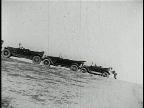 B/W 1925 long shot man (BIlly Bevan) pushing group of cars bumper to bumper up steep hill / feature
