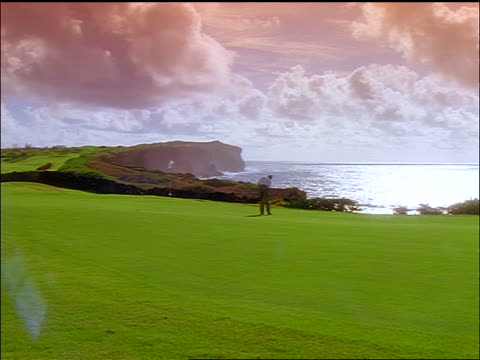 long shot man putting on green with ocean + cliffs in background / Poipu Bay Resort, Kauai