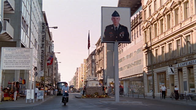 Long shot man riding Vespa down street past poster of soldier / Berlin, Germany