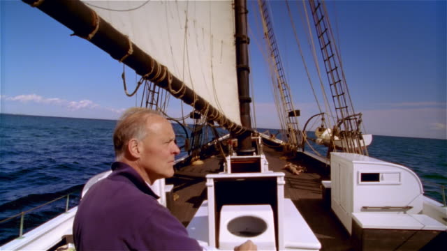 long shot man standing at helm of tall ship / looking around - helm stock videos and b-roll footage