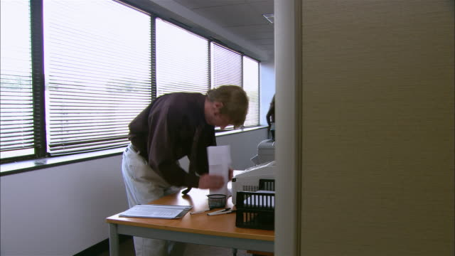 long shot man using fax machine as co-workers mill about in background - fax machine stock videos & royalty-free footage