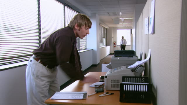 long shot man using fax machine / getting frustrated at broken machine / co-worker walking past unsympathetically - hanging up stock videos & royalty-free footage