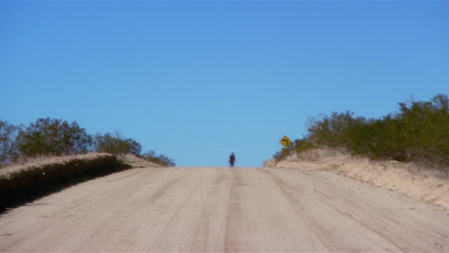 long shot man with guitar walking on desert road - heat haze stock videos & royalty-free footage