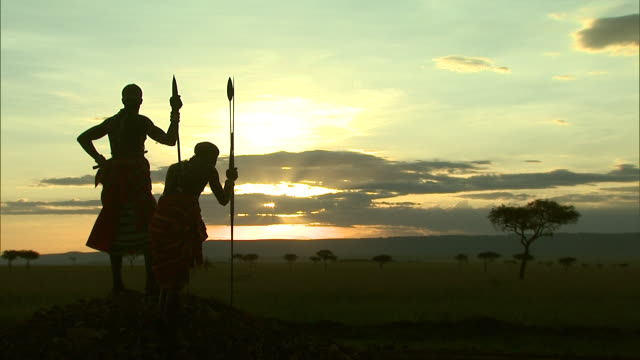 Long Shot - Massai tribesmen overlook an African savanna / Kenya