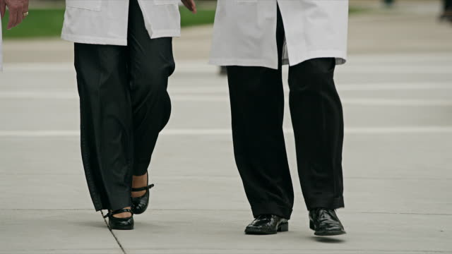 long shot, medical professionals wearing white lab coats walk in front of modern health facility - laborkittel stock-videos und b-roll-filmmaterial