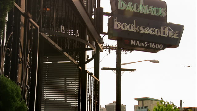 Long shot medium shot Bauhaus Books & Coffee sign / tilt down man reading newspaper in front of cafe / Seattle