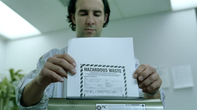 vídeos y material grabado en eventos de stock de long shot medium shot man shredding paper that says 'hazardous waste' / inpecting shredder / tie getting caught - shirt and tie