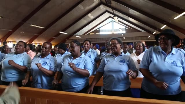 Long Shot members of the congregation sing during Sunday service on a national day of prayer for Nelson Mandela at Regina Mundi Church in Soweto on...
