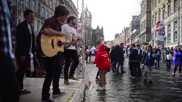 long shot members of the last embrace folk musical perform on the royal mile street entertainers perform on edinburgh's royal mile during the city's... - マイル点の映像素材/bロール