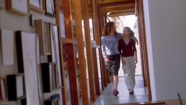 long shot mother and daughter walking down hall toward cam - figlia femmina video stock e b–roll