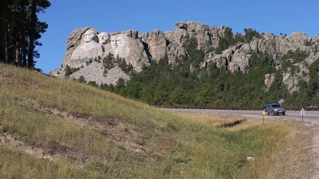 long shot, mount rushmore national memorial towers over the south dakota landscape on october 1, 2013 near keystone, south dakota. mount rushmore and... - マウントラシュモア国立記念碑点の映像素材/bロール