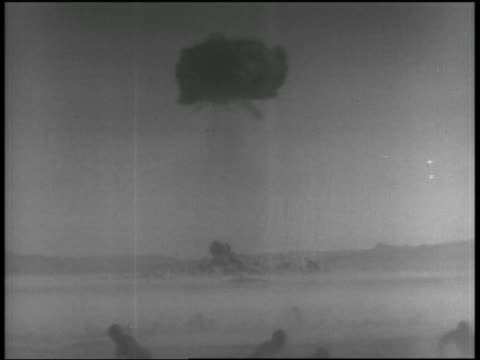 long shot mushroom cloud of atomic explosion test / soldiers standing up in foreground / nevada - 1955 stock videos & royalty-free footage