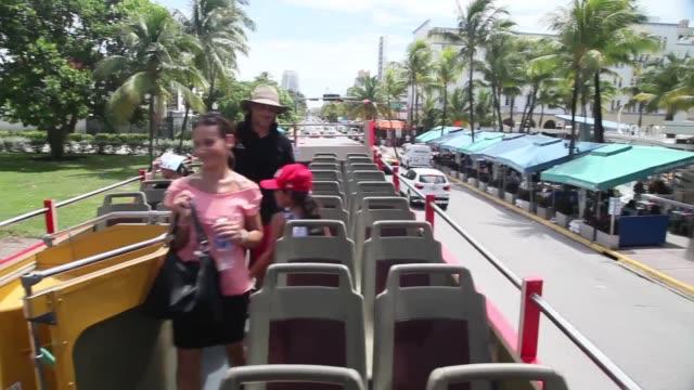 Long Shot Mustafa Bachiri and his wife Laetitia Bachiri enjoy their family vacation onboard a Big Bus Tour double decker bus during a sightseeing...