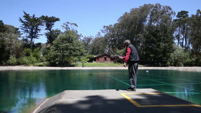 long shot of a angler practising casting. the golden gate angling & casting club located in the heart of beautiful golden gate park in san francisco... - fishing rod stock videos & royalty-free footage