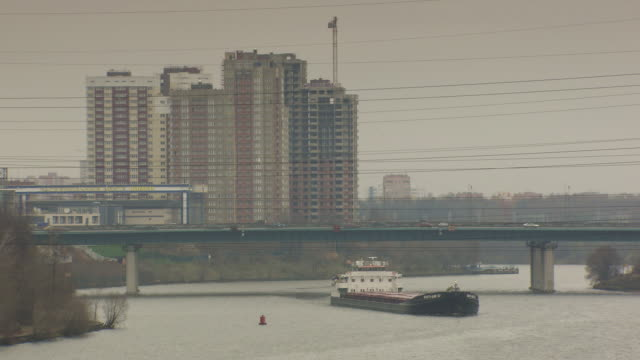 long shot of a cargo ship travelling under a bridge. moscow. - moscow russia stock videos and b-roll footage