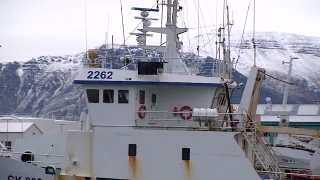 vídeos de stock, filmes e b-roll de long shot of a commercial fishing boat moored at a commercial dock in reykjavik - indústria da pesca