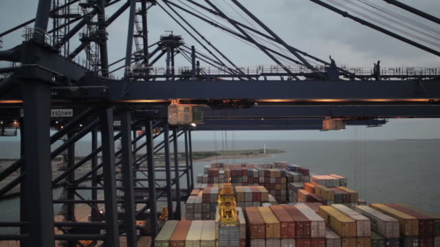 long shot of a crane lifting a container onto a ship at the port of felixstowe. - shipping stock videos & royalty-free footage