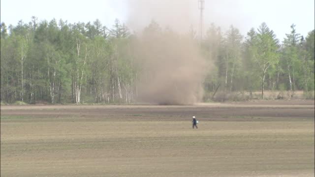 long shot of a dust devil swirling through a farm, japan - dammstorm storm bildbanksvideor och videomaterial från bakom kulisserna