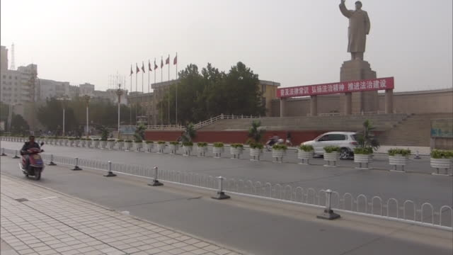 long shot of a large statue of mao zedong with upraised arm looking over renmin park from the main thoroughfare cars buses and moterbikes passing by... - mao stock videos and b-roll footage