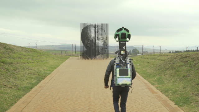vidéos et rushes de long shot of a man with a google trekker at the nelson mandela capture site - sculpture production artistique
