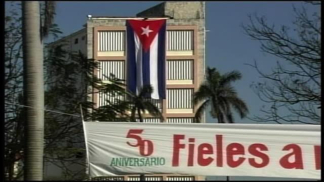 vidéos et rushes de long shot of a national flag telling the 50th anniversary of cuban revolution hanging in mid air - révolution cubaine