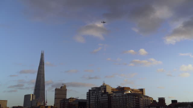 Long shot of a passenger aircraft flying over London's Shard building.