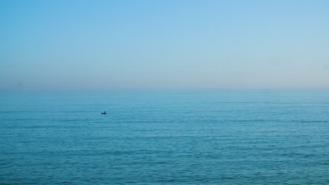 vídeos de stock e filmes b-roll de long shot of a person kayaking off brighton beach, uk. - canal mar