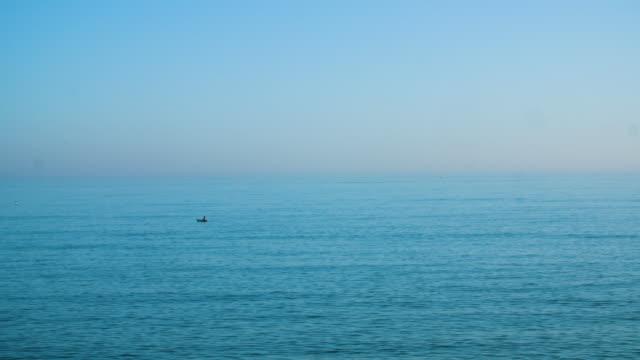 long shot of a person kayaking off brighton beach, uk. - ruderboot stock-videos und b-roll-filmmaterial