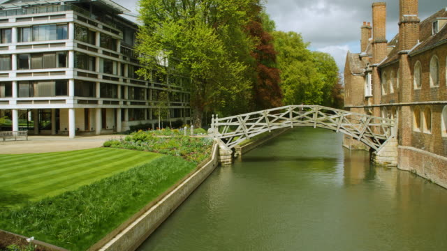 long shot of a person walking over the mathematical bridge at queen's college, cambridge. - bridge built structure stock videos & royalty-free footage