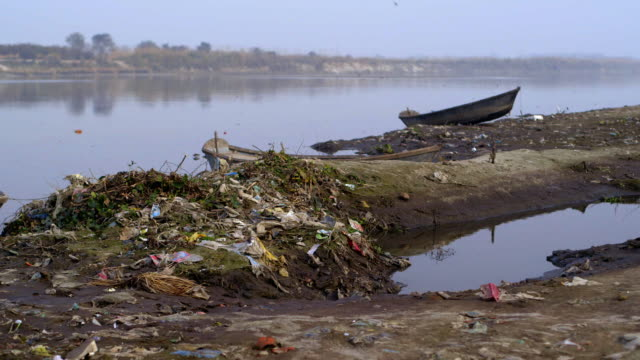 Long shot of a pile of rubbish washed up onto the shores of the Ganges River.