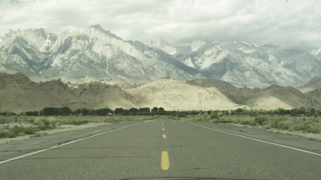Long shot of a road leading towards mountain range in Death Valley, Eastern California.