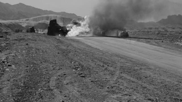 vídeos de stock e filmes b-roll de long shot of a road through desert possibly vehicle on fire - impacto