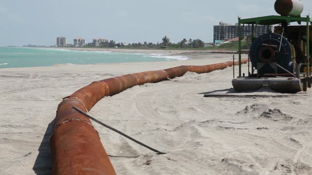 Long shot of a rusty discharge pipe A discharge pipe is used to carry dredged sand into place during a federally funded shore protection project by...