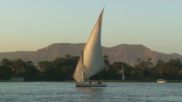 vidéos et rushes de long shot of a sail boat passing by on the nile river - égypte